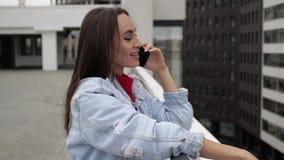 Muchacha que habla en el teléfono en el tejado metrajes