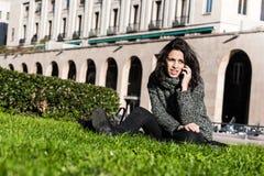 Muchacha que habla en el teléfono y que se sienta en hierba verde Fotografía de archivo