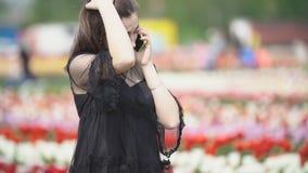 Muchacha que habla en el tel?fono en el campo del tulip?n metrajes