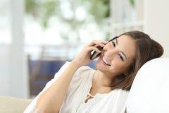 Muchacha que habla en el teléfono móvil en casa Foto de archivo libre de regalías