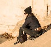 Muchacha que habla en el teléfono y que se sienta en las escaleras - filtro caliente - visión trasera Imagen de archivo libre de regalías