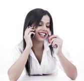 Muchacha que habla en la célula mientras que come Fotografía de archivo libre de regalías