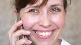 Muchacha que habla en risas de un teléfono celular, primer de los dientes mujer que habla en el smartphone y el primer sonriente  fotos de archivo libres de regalías