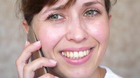 Muchacha que habla en risas de un teléfono celular, primer de los dientes mujer que habla en el smartphone y el primer sonriente  foto de archivo