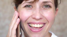 Muchacha que habla en risas de un teléfono celular, primer de los dientes mujer que habla en el smartphone y el primer sonriente  imagen de archivo libre de regalías