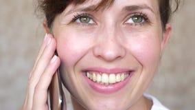 Muchacha que habla en risas de un teléfono celular, primer de los dientes mujer que habla en el smartphone y el primer sonriente  imagenes de archivo