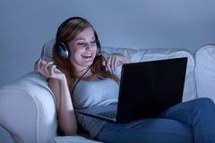 Muchacha que habla en Skype en la noche Imagen de archivo