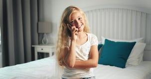 Muchacha que habla en smartphone en dormitorio metrajes