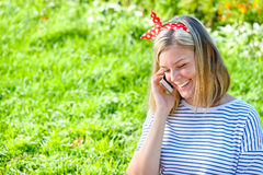 Muchacha que habla en un teléfono adentro al aire libre Fotos de archivo libres de regalías