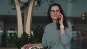 Muchacha que habla en un teléfono móvil en el salón del aeropuerto almacen de metraje de vídeo