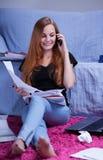 Muchacha que habla por el teléfono durante el aprendizaje Imagenes de archivo