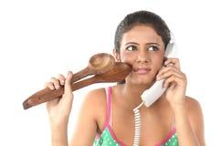 Muchacha que habla sobre el teléfono con los palillos de madera Imagen de archivo