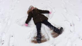 Muchacha que hace ángel de la nieve almacen de metraje de vídeo