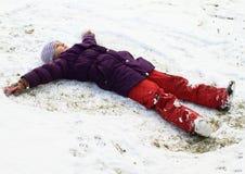 Muchacha que hace ángel en nieve Imágenes de archivo libres de regalías