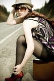Muchacha que hace autostop con la maleta Imagen de archivo libre de regalías