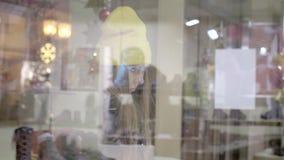 Muchacha que hace compras de la ventana metrajes