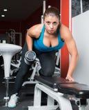 Muchacha que hace ejercicio con pesas de gimnasia en sitio de la aptitud F atractiva Foto de archivo