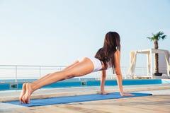 Muchacha que hace ejercicios de la yoga en la estera de la yoga Fotografía de archivo libre de regalías