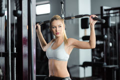 Muchacha que hace ejercicios en ella detrás en el gimnasio Fotos de archivo