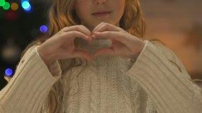 Muchacha que hace el corazón con las manos, el concepto de amor de la familia y el cuidado en los días de fiesta de Navidad almacen de metraje de vídeo