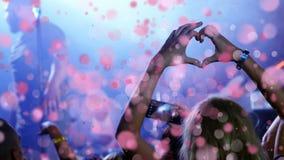 Muchacha que hace el corazón con sus manos al cantante en el concierto con la animación de la burbuja