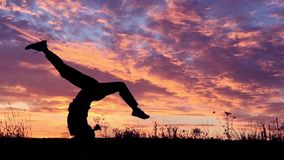 Muchacha que hace el elemento acrobático en la puesta del sol Cámara lenta metrajes