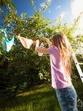 Muchacha que hace el lavadero y la ropa de sequía en el jardín Imagen de archivo