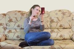 Muchacha que hace el maquillaje que se sienta en el sofá Fotografía de archivo