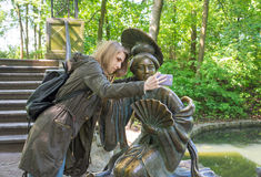 Muchacha que hace el selfie con una estatua Foto de archivo