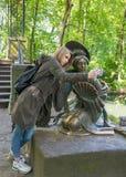 Muchacha que hace el selfie con una estatua en el parque Imagen de archivo