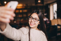 Muchacha que hace el selfie de la foto, vidrios del inconformista en café Imágenes de archivo libres de regalías