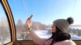 Muchacha que hace el selfie en la carlinga de una noria en la sonrisa del teléfono almacen de video