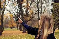 Muchacha que hace el selfie en un parque en otoño Imagen de archivo