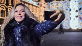 Muchacha que hace el selfie usando móvil al aire libre en el fondo de la exposición luminosa de la decoración de la tarde de la N almacen de video