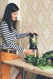 Muchacha que hace el smoothie verde en una licuadora imagen de archivo libre de regalías