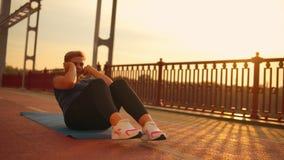 Muchacha que hace entrenamiento del ab en el puente metrajes