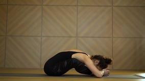 Muchacha que hace estirar en la posici?n sentada Yoga practicante de la mujer bonita joven en el sitio de clase minimalista liger almacen de metraje de vídeo