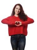 Muchacha que hace forma del corazón con sus manos Fotografía de archivo