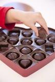 Muchacha que hace furtivamente un chocolate Fotografía de archivo libre de regalías