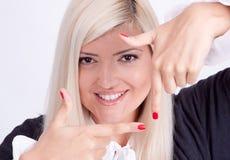 Muchacha que hace gesto del marco con las manos Imagenes de archivo