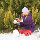 Muchacha que hace la bola de la nieve Imágenes de archivo libres de regalías