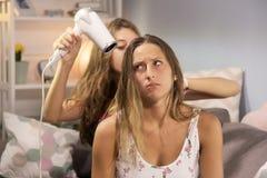 Muchacha que hace la cara divertida mientras que la novia se está secando el pelo largo Fotos de archivo libres de regalías