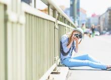 Muchacha que hace la foto con la cámara retra mientras que se sienta en la calle de la ciudad Imagen de archivo libre de regalías