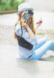 Muchacha que hace la foto con la cámara retra mientras que se sienta en las escaleras Foto de archivo
