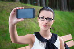 Muchacha que hace la foto del selfie en el teléfono móvil Fotografía de archivo