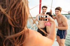 Muchacha que hace la imagen de sus amigos que se divierten en el yate Imagenes de archivo