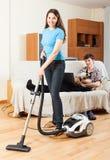 Muchacha que hace la limpieza del piso mientras que hombre que descansa sobre el sofá Foto de archivo libre de regalías