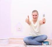 Muchacha que hace la muestra ACEPTABLE en la renovación de la casa Foto de archivo libre de regalías
