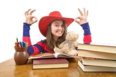 Muchacha que hace la muestra aceptable que se sienta en la tabla con la pila de libros Imagen de archivo libre de regalías