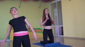 Muchacha que hace la parte posterior de la desviación en las esteras en un gimnasio 4K metrajes